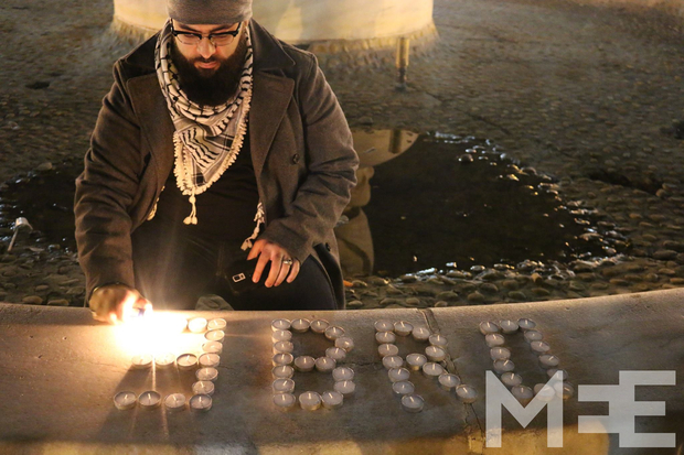 A mourner arranges candles at the Washington, DC vigil (MEE/Ilana Alazzeh)